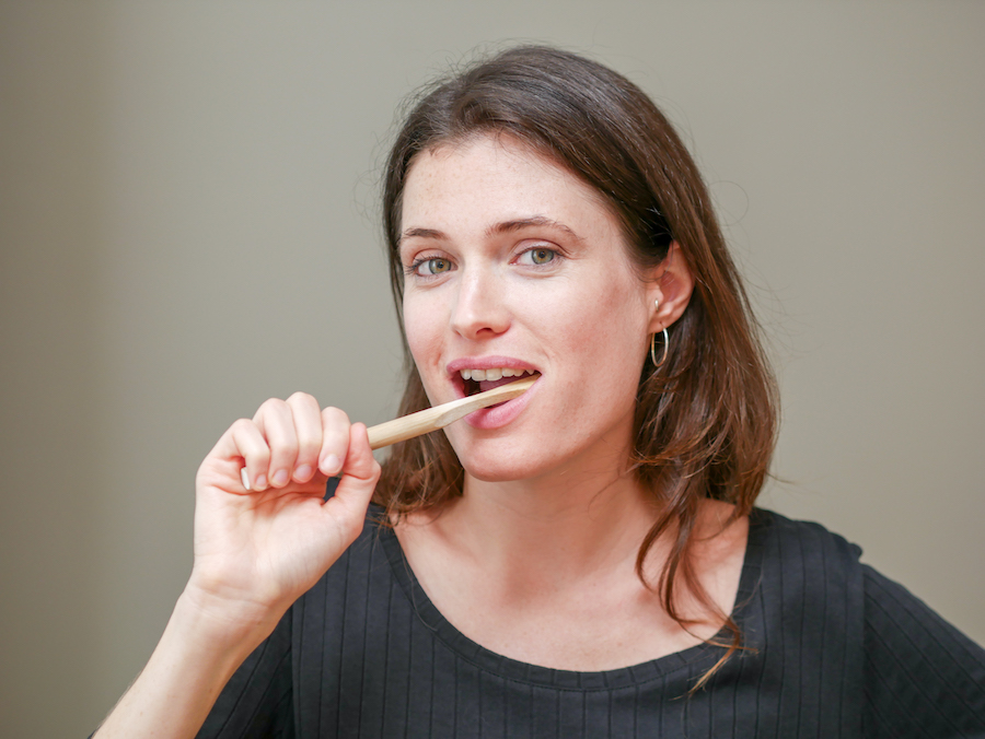 girl brushing teeth with a plastic free bamboo toothbrush