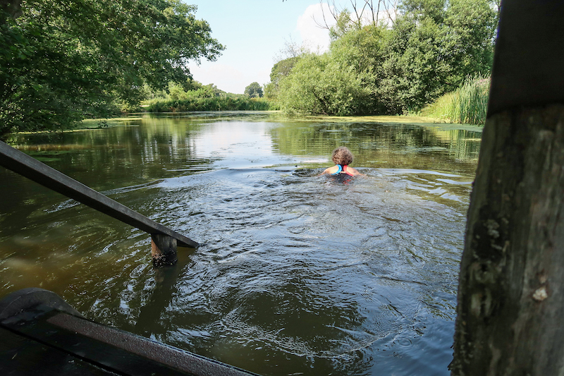 woman swimming in natural swimming pond